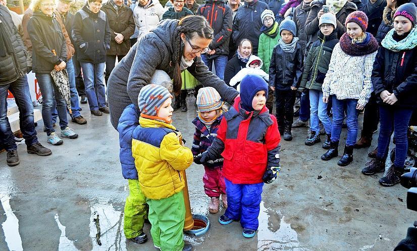 Die Kinder Eddi, Erik, Lennard und Ella versenken gemeinsam mit Ortsvorsteherin Carolin Hansch eine Dokumentenhülse.