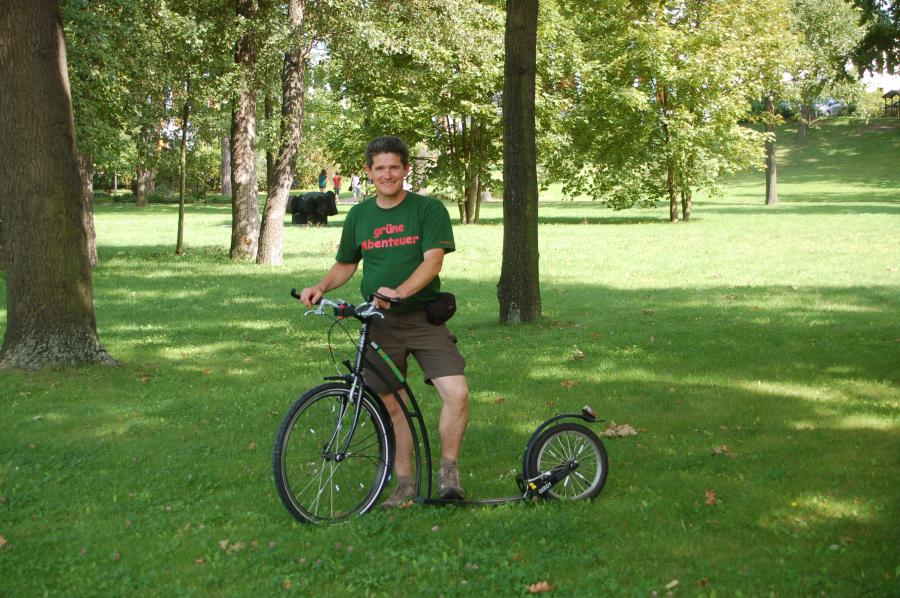 Der grüne Lutz unterwegs mit dem Tretroller
