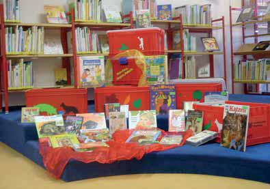 Auf dem Bild sieht man vier rote Boxen, die teilweise mit verschiedenen Motiven beklebt sind,  und davor stehen bzw. liegen einige Bücher.