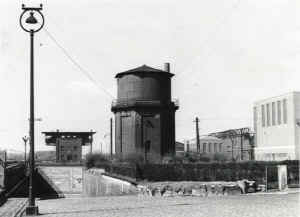 Blick in westlicher Richtung auf das Bahnhof- und Zechengelände. Der Wasserturm wurde 1958 abgebrochen, hinten links das Stellwerk Hz (1936-1978), rechts das Walzwerk Caroline der Firma Wiederholt (Gelände der ehemaligen Zeche Caroline)   Links unten die Auffahrt aus der Unterführung zum Bahnhof.