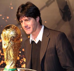 Fast andächtig bestaunt Joachim Löw den Fussball Weltpokal - der Vertrag mit dem DFB ist verlängert, gerne würde er den Pokal ein zweites Mal gewinnen - Foto: johapress / Hahne