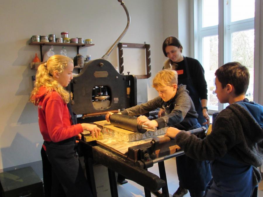 Schüler*innen an der Druckpresse, Foto: Museum Neuruppin