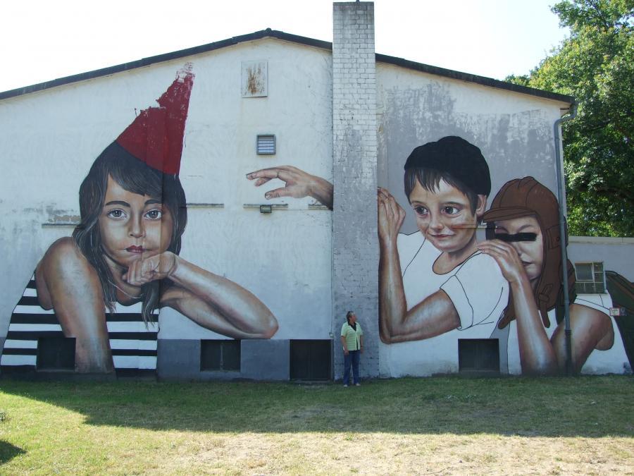 Bild zeigt Künstlerin mit ihrem Kunstwerk an der Rückseite der Turnhalle