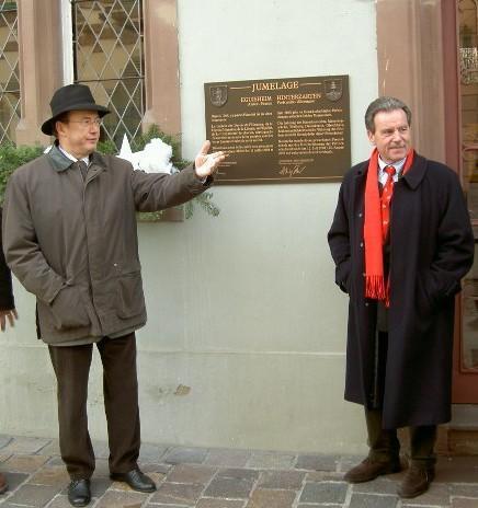 Bürgermeister Pierre Hussherr (Eguisheim) und Hansjörg Eckert (Hinterzarten) vor der Tafel der Freundschaft an der Fassade des Hinterzartener Rathauses