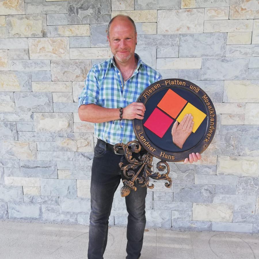 Firmenchef mit Zunftschild für das Fliesen-, Platten- und Mosaiklegerhandwerk