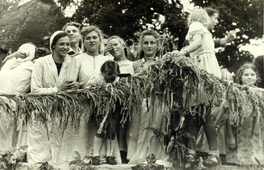 Fröhliche junge Landfrauen auf einem Erntefest-Wagen