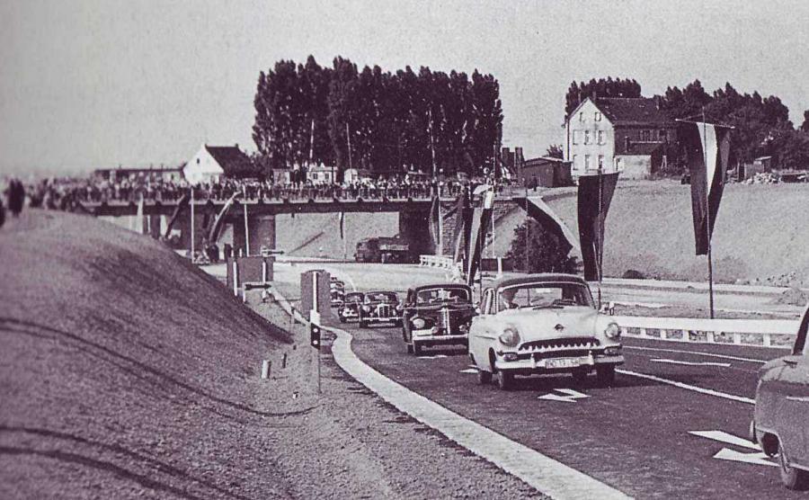 Bild vom 20.07.1957 anläßlich der feierlichen Inbetriebnahme des BAB-Teilstückes der A1 von Kamen nach Unna aufgenommen. im Hintergrund der Schrankenposten 186 am Obermassener Kirchweg in Unna. In der Bildmitte vor den Bäumen kann man noch deutlich die Schrankenbäume sehen.
