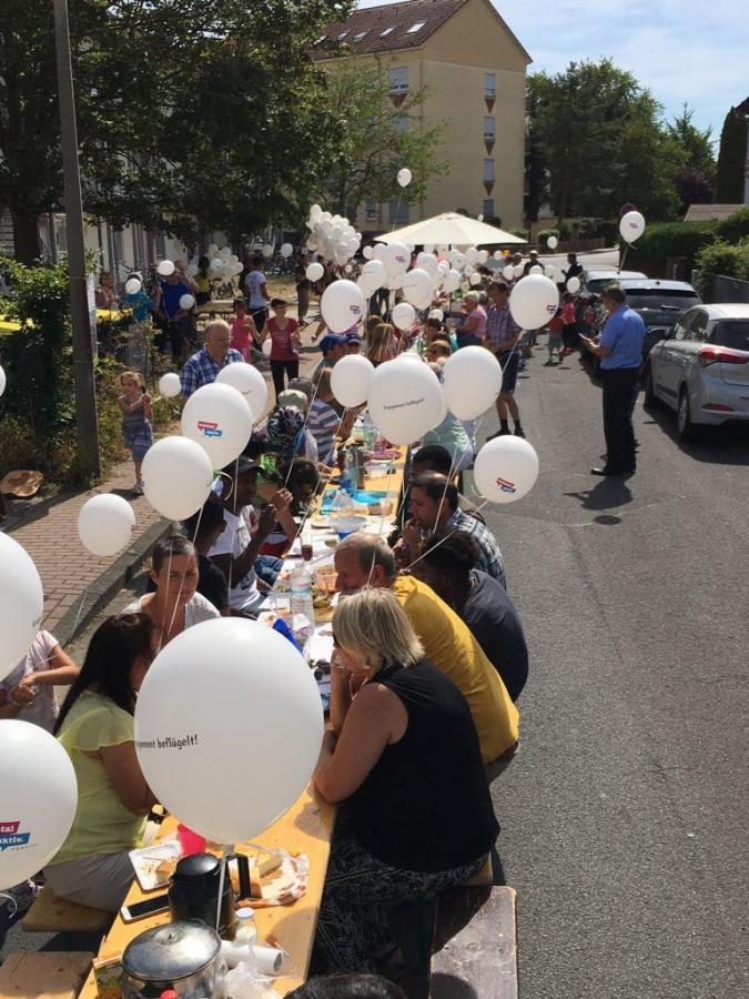 Bild zeigt die lange Tafel mit vielen Menschen und Luftballons