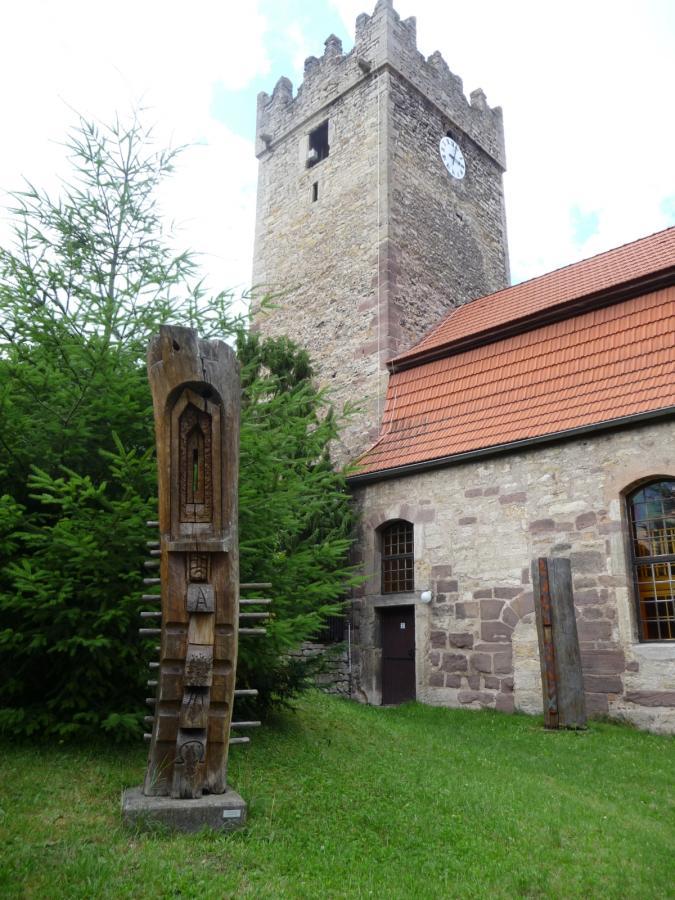 Ostseite mit Holzskulptur im Kirchhof
