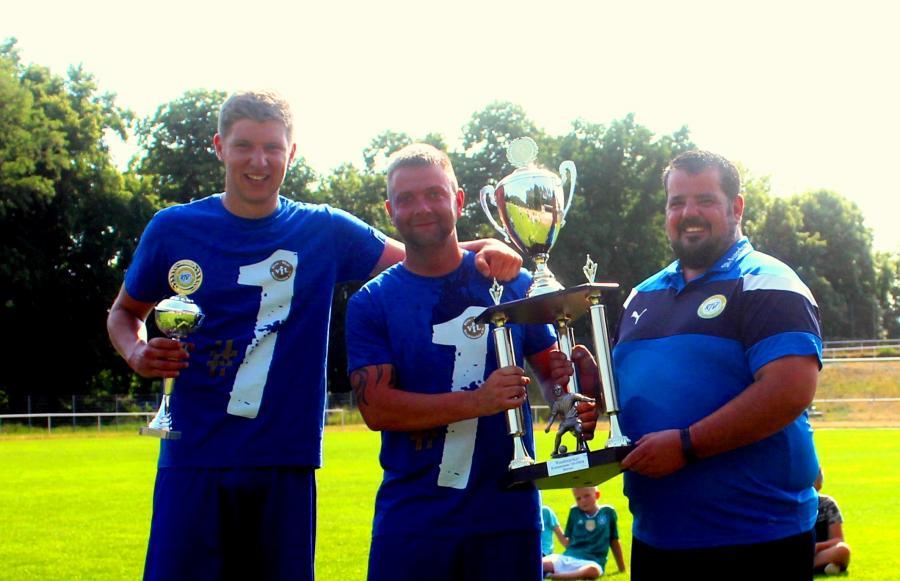 Andreas Knothe vom Spielausschuss des Kreisfussballverbandes übergibt Neuklosters Kapitän Benjamin Krohn den Meisterpokal. Links Markus Nicolai.