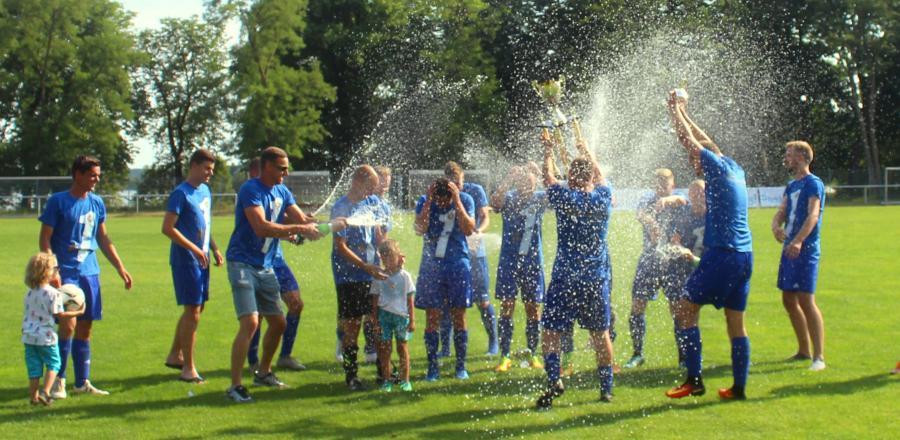 Der VfL Blau Weiß Neukloster wurde Meister in der Kreisoberliga. Die Spieler feiern die Meisterschaft mit einer Sektdusche