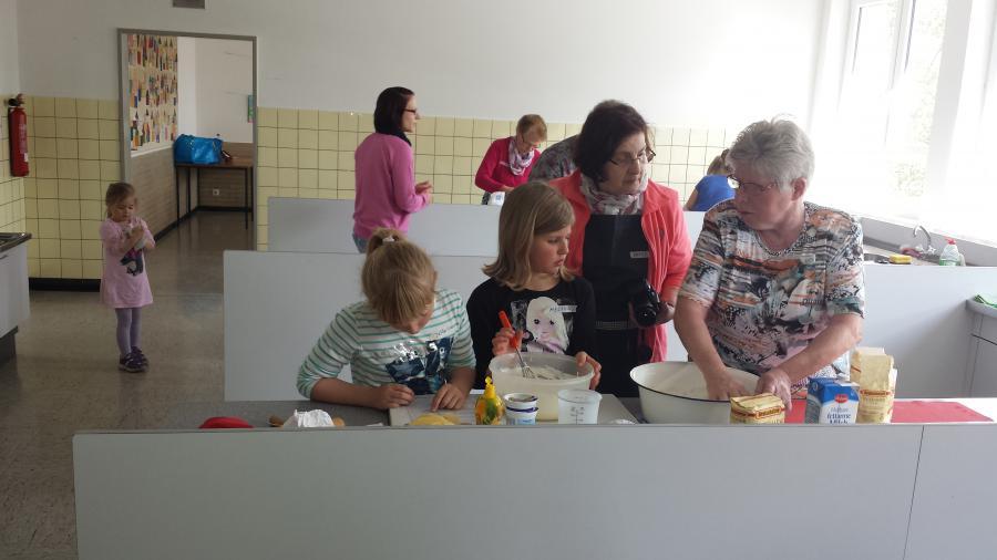 Landfrauen und Kinder backen Flammkuchen