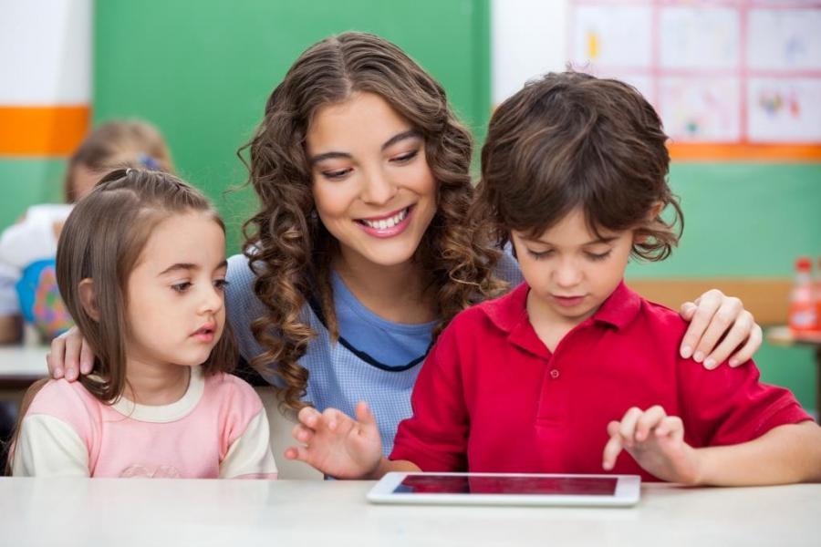 Kinder und Erzieherin mit Tablet
