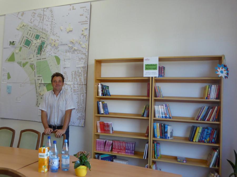 Der Quartiersmanager Jörg Mose vor dem öffentlichen Bücherregal und dem Modell von Kyritz-West