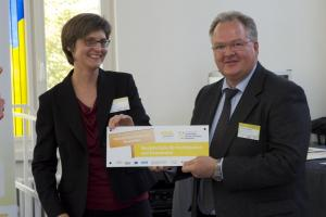 Nadja Damm von der Deutschen Kinder- und Jugendstiftung übereicht Rektor Gerhard Schmidt die Auszeichnung