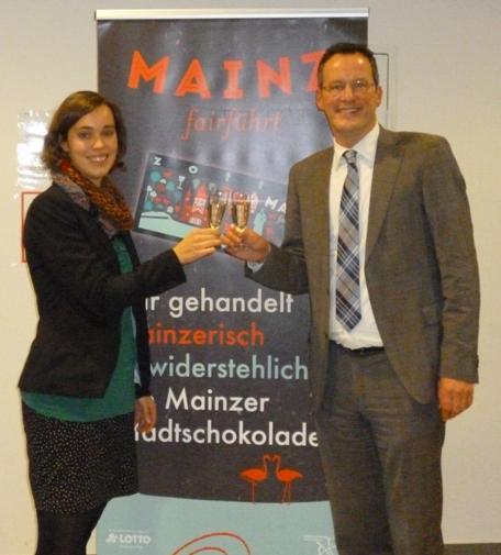 Der Mainzer Oberbürgermeister Michael Ebling und Stefanie Bartlett vom Weltladen Unterwegs stoßen gemeinsam auf die Mainzer Stadtschokolade an