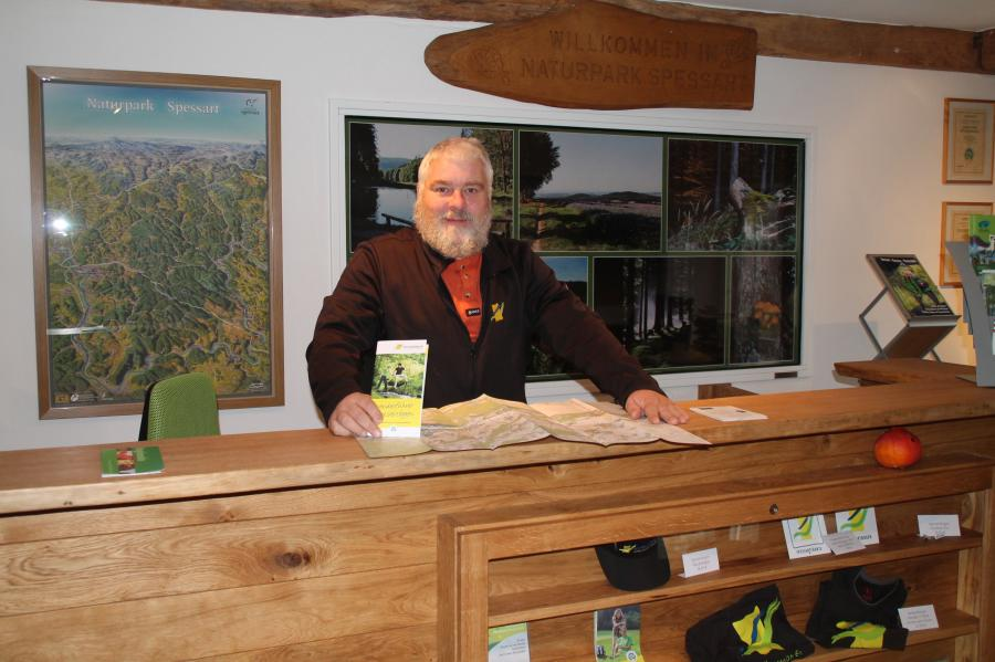 Naturpark-Geschäftsführer Fritz Dänner hinter der Info-Theke des Naturparks Spessart – dort erhalten Sie Informationen zum Wandern und Mountainbiken, sowie Flyer, Jahresprogramm, Karten und Bücher.